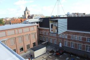Container die drie verdiepingen hoog aan kraan hangt boven binnenplaats ziekenhuis