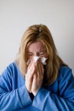 vrouw niest met een zakdoek voor de mond