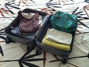 Openliggende valies met handdoeken, pyjama, toiletzak