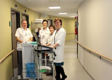 Artsen en verpleegkundigen rond een pc in het ziekenhuis