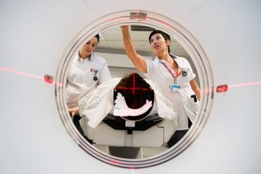 Een patiënt bij een CT-onderzoek, met twee verpleegkundigen aan zijn zijde.