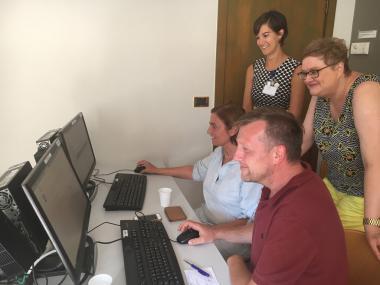Foto van medewerkers en patiënten bij pc