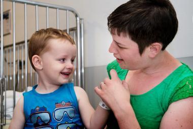 Mama met kind op schoot in een kamer op de kinderafdeling