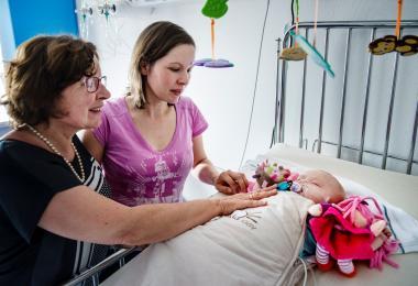 Een mama en een oma bij een kindje dat in bed ligt in de kinderafdeling