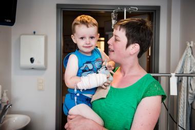Een mama met een kindje op de arm in de kinderafdeling