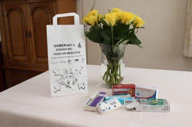 Een medicatiezak en geneesmiddelen op een tafel in een living