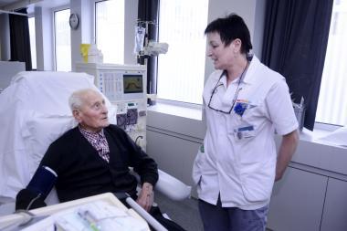 Nierdialysepatient in een zetel met een verpleegkundige