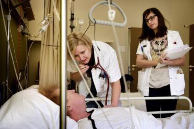 Een arts luistert voorovergebogen naar een patiënt in bed