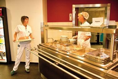 Een mevrouw van de bediening slaat een praatje met een personeelslid in het restaurant op campus Brugsesteenweg