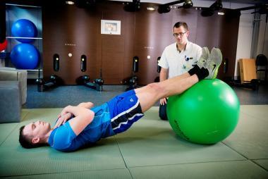 Een patiënt oefent met een bal bij een kinesist