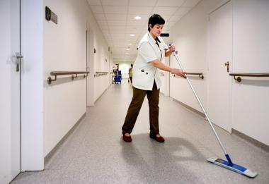 Een schoonmaakster aan het werk in een gang van het ziekenhuis