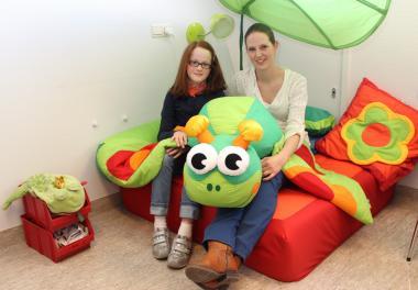 Een begeleidster en een kindje zitten samen in een zetel in een knus hoekje