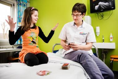 Verpleegkundige bij een spelend kind dat op bed zit