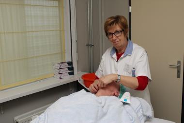 Een vrijwilligster geeft een patiënte een gelaatsverzorging