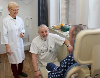 Twee vrijwilligers praten met een patiënt
