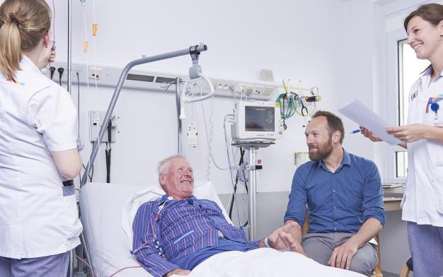 Dr. Deeren en enkele verpleegkundigen bij het bed van een patiënt