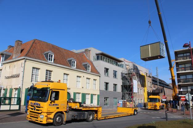 Een grote container wordt over het gebouw gehesen