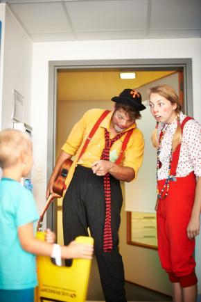 Twee clowns op bezoek bij een jongetje op de kinderafdeling