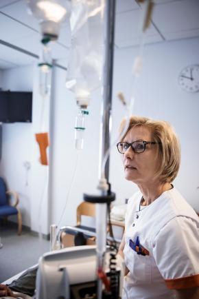 Verpleegkundige controleert chemo bij patiënt