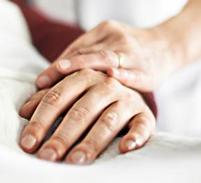 Hand verpleegster op hand patient die in bed ligt