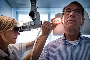 Foto van neus-keel-oor specialist die patiënt onderzoekt
