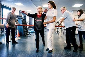 Kinesist geeft revalidatie-oefeningen aan patiënten